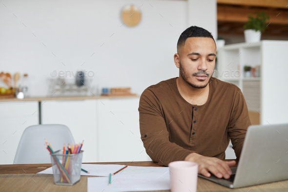 Handsome Mixed-Race Man Using Laptop at Home - Stock Photo - Images