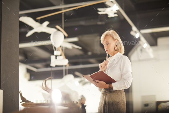 Female Art Gallery Manager Reading Book - Stock Photo - Images