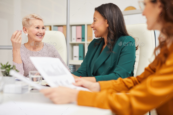 Cheerful Colleagues Chatting While Working - Stock Photo - Images