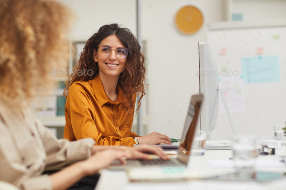 Two Charming Women Interacting While Working - Stock Photo - Images