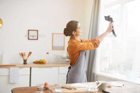 Young Woman Filming Vlog in Kitchen - Stock Photo - Images