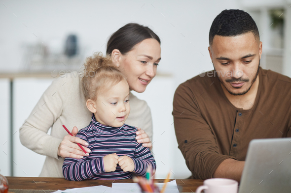 Mixed-Race Family Using Laptop at Home - Stock Photo - Images