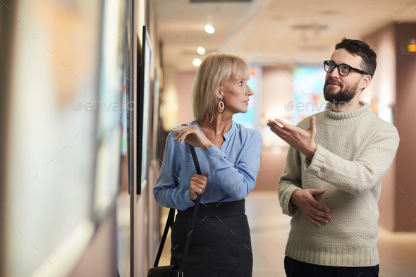 People Discussing Paintings in Art Gallery - Stock Photo - Images