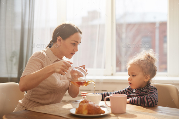 Loving Mother Enjoying Breakfast with Cute Little Daughter - Stock Photo - Images