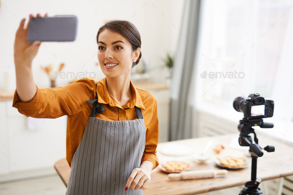 Smiling Woman Vlogging in Kitchen - Stock Photo - Images