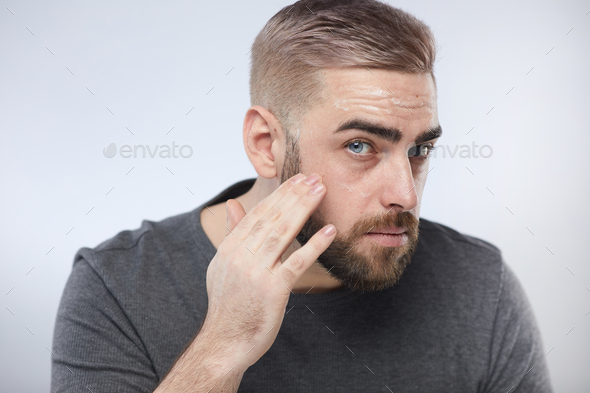 Confident Man Using Skincare Product - Stock Photo - Images