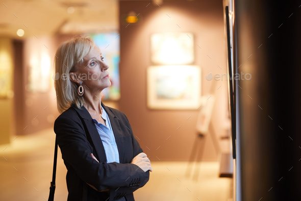 Mature Woman Looking at Paintings in Art Gallery - Stock Photo - Images