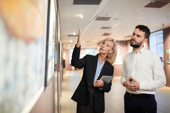 Experts Discussing Paintings in Art Gallery - Stock Photo - Images
