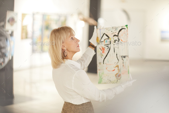 Elegant Woman Holding Painting in Art Gallery - Stock Photo - Images