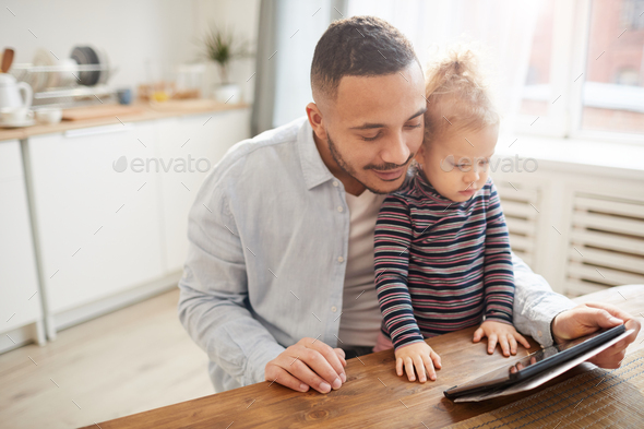 Caring Father Using Digital Tablet with Cute Little Girl - Stock Photo - Images