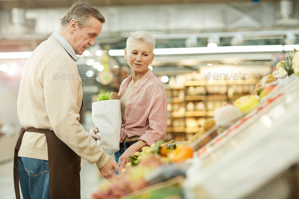 Mature Woman Buying Groceries at Market - Stock Photo - Images