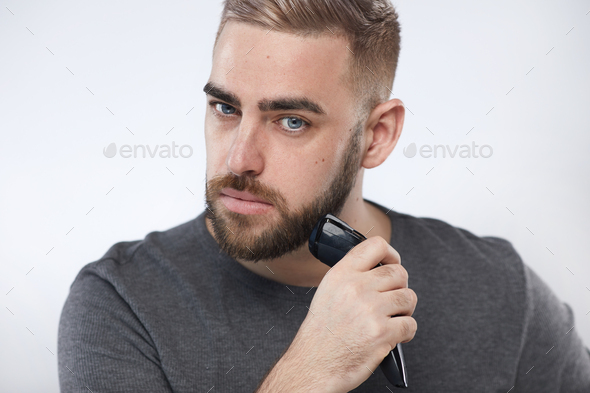 Young Man Trimming Beard - Stock Photo - Images