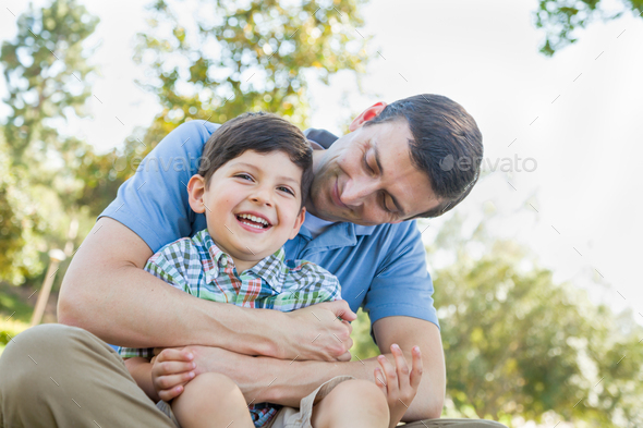 Loving Young Father Tickling Son in the Park. - Stock Photo - Images