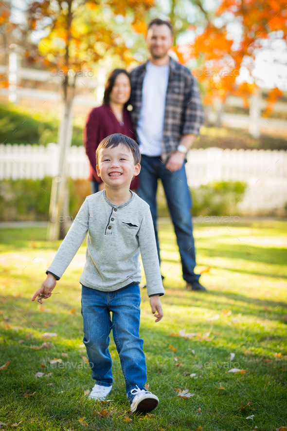 Outdoor Portrait of Happy Mixed Race Chinese and Caucasian Parents and Child. - Stock Photo - Images