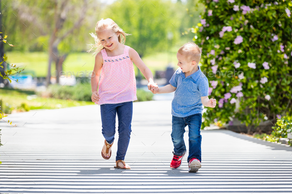 Young Sister and Brother Holding Hands And Running At The Park - Stock Photo - Images