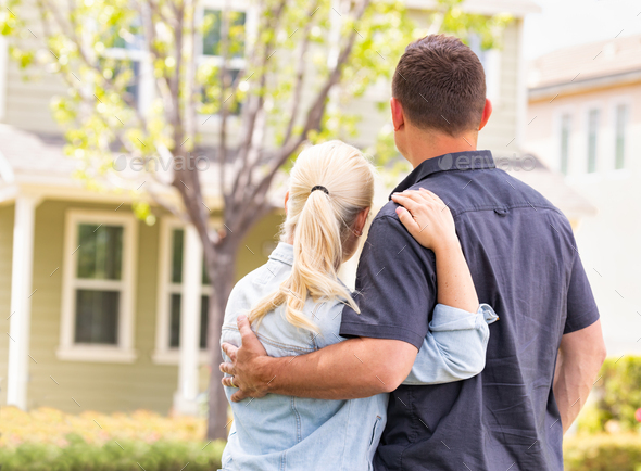 Happy Caucasian Couple Facing Front of House - Stock Photo - Images
