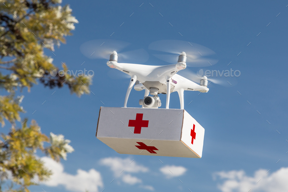 Unmanned Aircraft System (UAS) Quadcopter Drone Carrying First Aid Package In The Air. - Stock Photo - Images