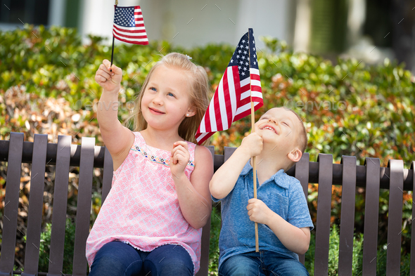 Young Sister and Brother Comparing Each Others American Flag Size On The Bench At The Park - Stock Photo - Images