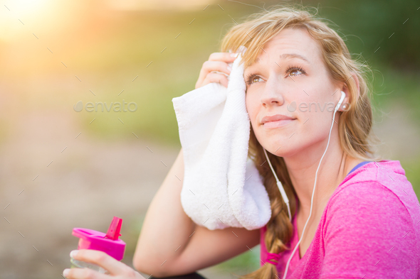 Woman Outdoors With Towel and Water Bottle in Workout Clothes Listening To Music with Earphones. - Stock Photo - Images