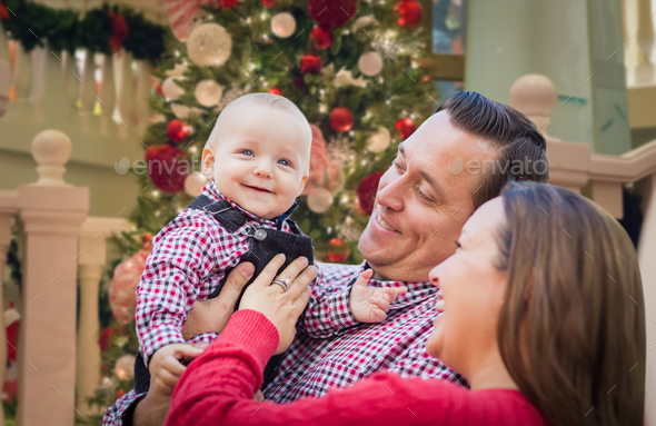 Happy Young Parents with Baby In Front of Decorated Christmas Tree. - Stock Photo - Images
