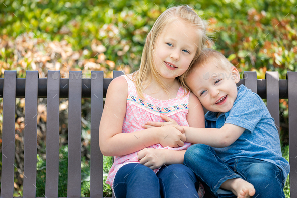 Young Sister and Brother Having Fun On The Bench At The Park - Stock Photo - Images