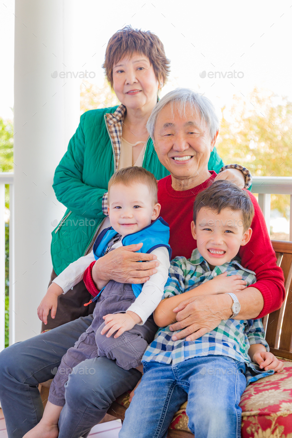 Senior Adult Chinese Couple Sitting With Their Mixed Race Grandchildren - Stock Photo - Images