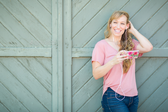 Young Adult Brown Eyed Woman Listening To Music with Earphones on Her Smart Phone. - Stock Photo - Images