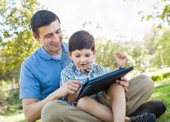 Happy Father and Son Playing on a Computer Tablet Outside. - Stock Photo - Images