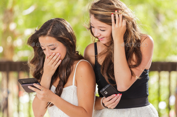 Two Expressive Mixed Race Girlfriends Using Their Smart Cell Phones Outdoors - Stock Photo - Images