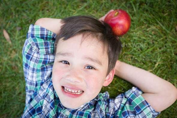 Mixed Race Chinese and Caucasian Young Boy With Apple Relaxing On His Back Outside On The Grass. - Stock Photo - Images