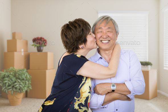 Happy Senior Chinese Couple Inside Empty Room with Moving Boxes and Plants. - Stock Photo - Images
