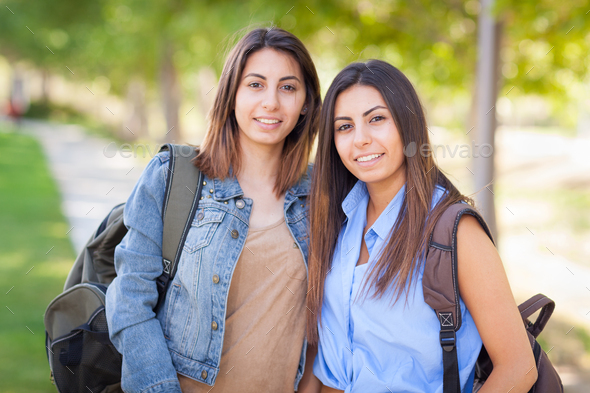 Two Beautiful Young Ethnic Twin Sisters With Backpacks Walking Outdoors. - Stock Photo - Images