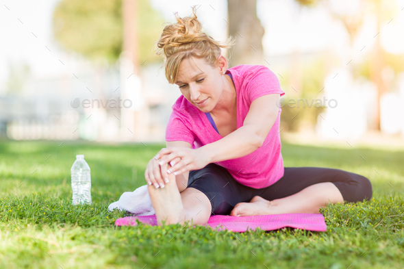 Young Fit Flexible Adult Woman Outdoors on The Grass With Yoga Mat Stretching Her Legs. - Stock Photo - Images