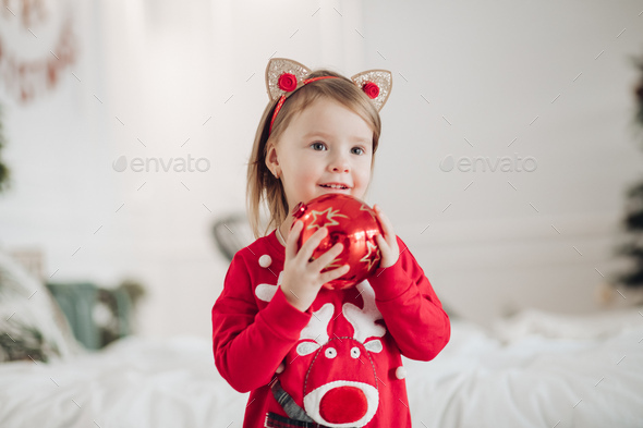 Lovely little girl in red dress with Christmas present - Stock Photo - Images