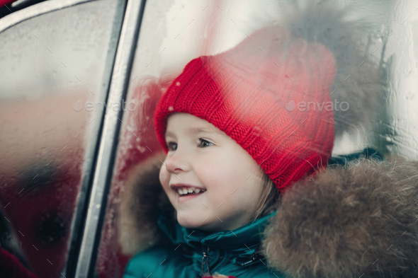 Smiling cute winter girl in red hat sitting in car having fun - Stock Photo - Images