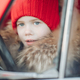 Smiling cute winter boy in red hat sitting in car having fun - PhotoDune Item for Sale