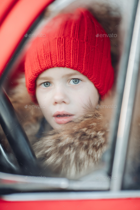 Smiling cute winter boy in red hat sitting in car having fun - Stock Photo - Images