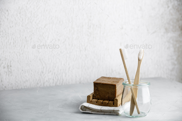 Eco-friendly bamboo toothbrushes in a glass jar and handmade organic soap, copy space - Stock Photo - Images