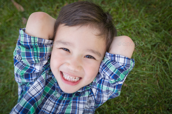 Mixed Race Chinese and Caucasian Young Boy Relaxing On His Back Outside On The Grass - Stock Photo - Images