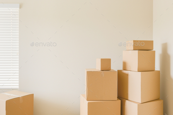 Variety of Packed Moving Boxes In Empty Room - Stock Photo - Images