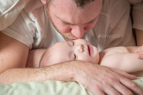 Mixed Race Chinese and Caucasian Baby Boy Laying In Bed with His Parents - Stock Photo - Images