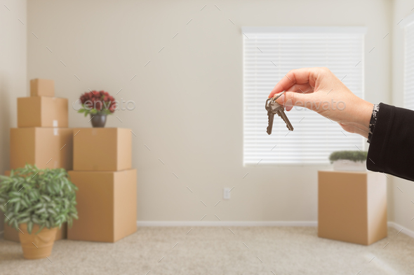Handing Over House Keys In Room with Packed Moving Boxes - Stock Photo - Images