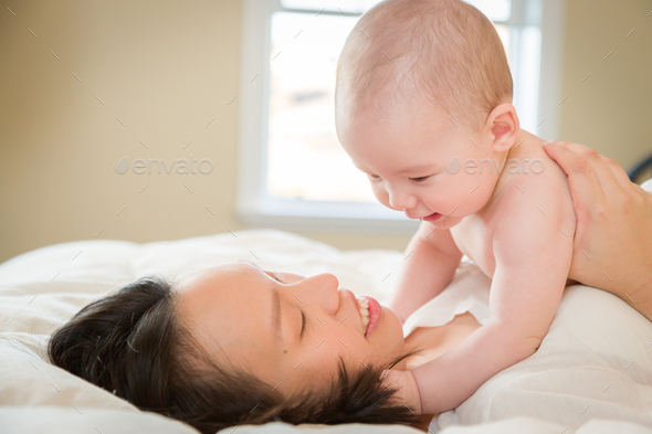 Mixed Race Chinese and Caucasian Baby Boy Laying In Bed with His Mother - Stock Photo - Images