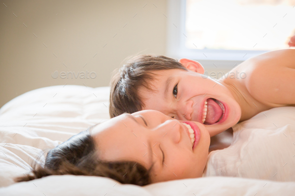 Mixed Race Chinese and Caucasian Boy Laying In His Bed with His Mother. - Stock Photo - Images
