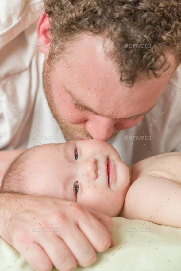 Mixed Race Chinese and Caucasian Baby Boy In Bed with His Father - Stock Photo - Images