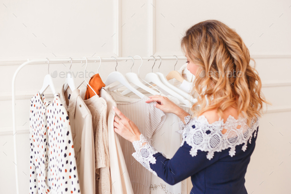 Young woman choosing clothes on a rack for the party. Designers shop or own wardrobe - Stock Photo - Images