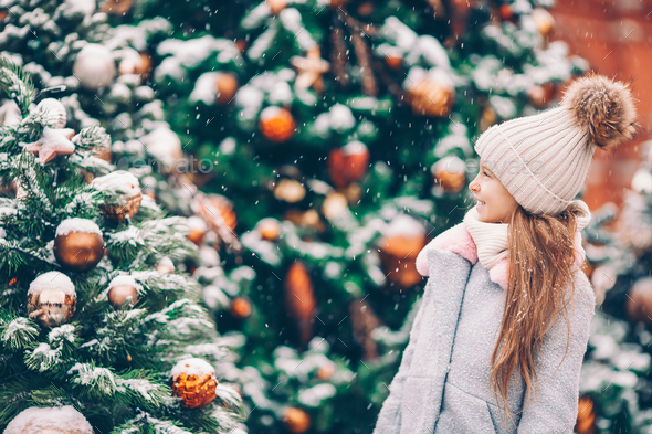 Little happy girl near fir-tree branch in snow for new year - Stock Photo - Images