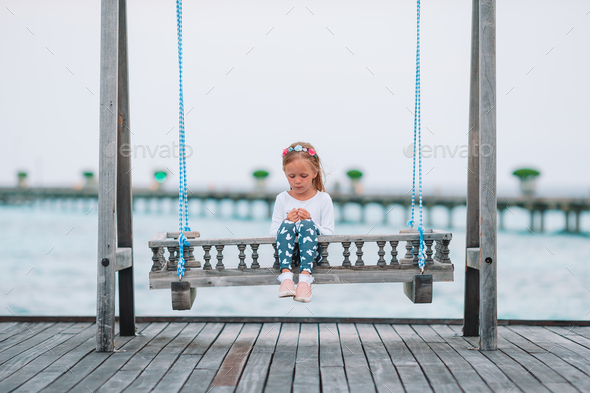 adorable little girl on swing at sunset - Stock Photo - Images