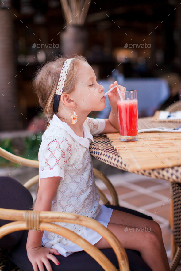 Adorable little girl drinking fruit cocktail outdoor - Stock Photo - Images