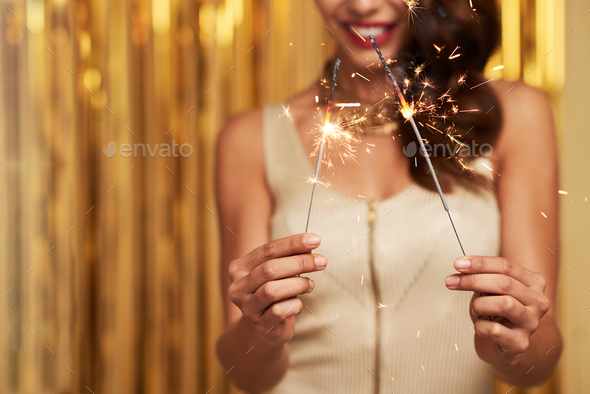 Party girl holding burning sparklers - Stock Photo - Images